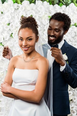 cheerful african american bridegroom touching white veil and smiling near bride and flowers