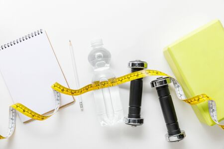 top view of water in bottle, measuring tape, dumbbells and blank notebook with pencil near box on white background