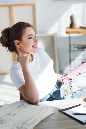 cheerful woman in white t-shirt holding magazine near fashion sketches on table