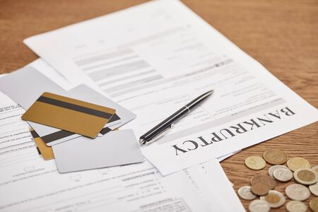 bankruptcy form among documents, credit cards and coins on wooden table Stockfoto