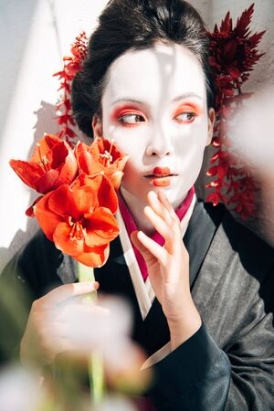 selective focus of sakura branches and beautiful geisha holding red flowers in sunlight