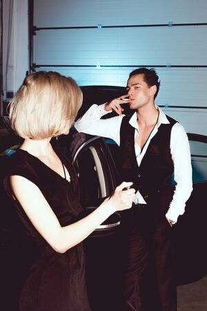 beautiful fashionable young woman holding lighter while handsome man smoking cigarette Banque d'images