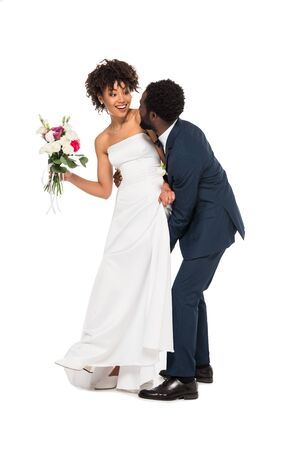 african american bridegroom touching happy bride with flowers isolated on white