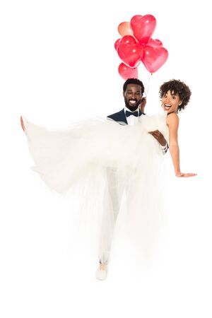happy african american bridegroom holding in arms bride in wedding dress with balloons  isolated on white 写真素材