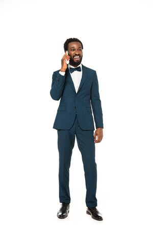 happy african american bridegroom talking on smartphone and standing isolated on white 版權商用圖片