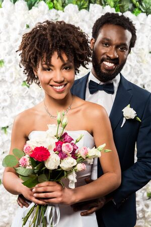 cheerful african american bride holding bouquet with flowers near bridegroom 写真素材