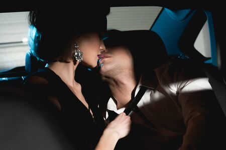 sensual man and young woman kissing in back seat of car in dark