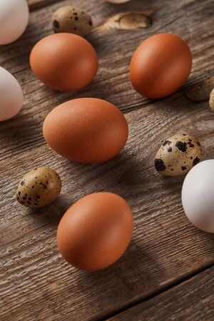 quail and chicken eggs on wooden table