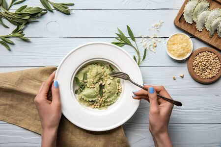 vista ritagliata di una donna che mangia ravioli verdi con pinoli e salvia vicino a formaggio grattugiato su un tavolo di legno bianco