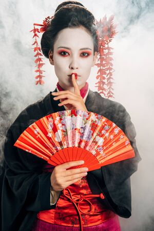 beautiful geisha in black kimono with flowers in hair holding hand fan and showing shh gesture in smoke