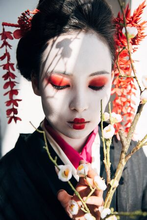 sakura branches and beautiful geisha with red and white makeup in sunlight