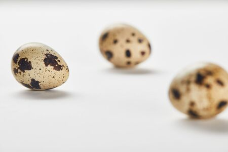 selective focus of quail eggs on white surface