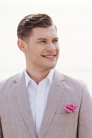 stylish smiling bridegroom in formal wear with boutonniere looking away