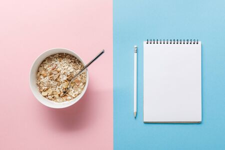 top view of breakfast cereal in bowl and blank notebook with pencil on blue and pink background Stock Photo
