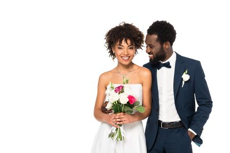 happy african american bride holding bouquet near bridegroom standing with hand in pocket  isolated on white