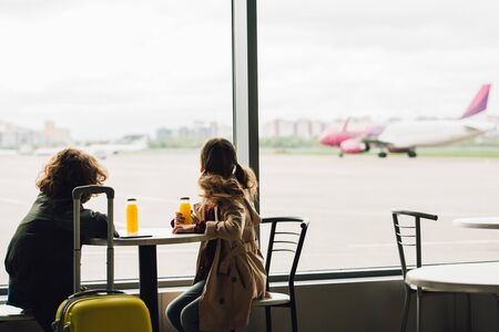 two kids sitting in waiting hall and looking out window on plane Imagens