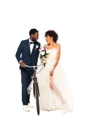 glücklicher afroamerikanischer Bräutigam in der Nähe einer fröhlichen Braut mit Blumen, die Fahrrad isoliert auf weiß hält Standard-Bild