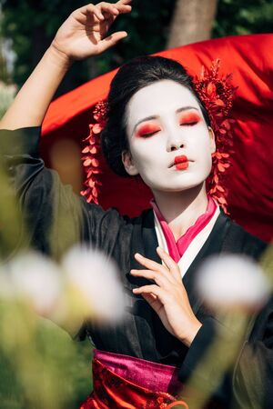 selective focus of tree branches and dancing geisha with red cloth on background in sunlight