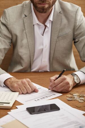 cropped view of bearded businessman in suit filling in bankruptcy form at wooden table