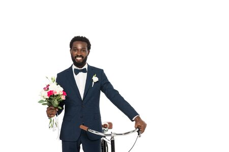 cheerful african american man holding bouquet and bicycle isolated on white