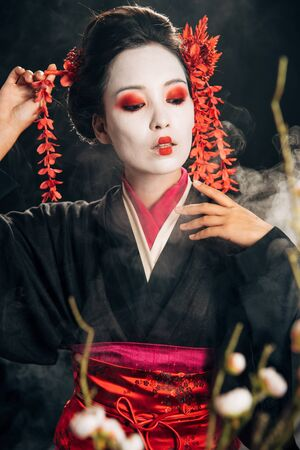 selective focus of beautiful geisha in black kimono with red flowers in hair and sakura branches on black background with smoke