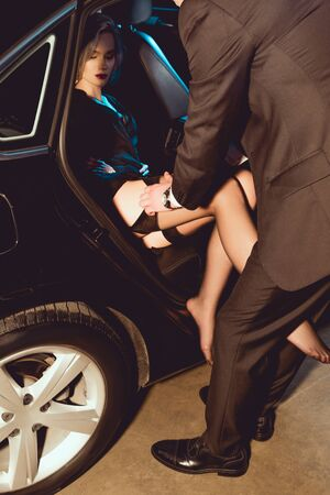 man undressing beautiful girl in stockings near car