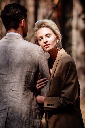 stylish blonde young woman with husband in forest