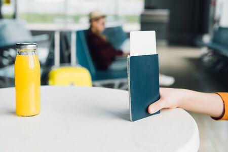 Cropped view of preteen kid holding passport and air ticket in airport on table with orange juice