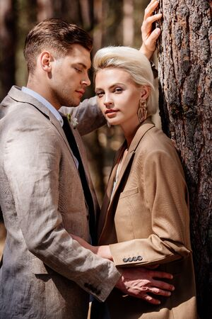 stylish couple in elegant jackets embracing in forest