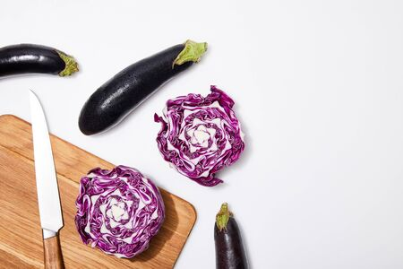 top view of red cabbage and eggplants on wooden chopping board and knife on white background Stock Photo