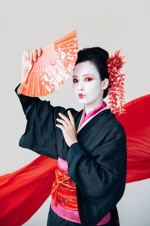 beautiful geisha in black kimono posing with hand fan and red cloth on background isolated on white