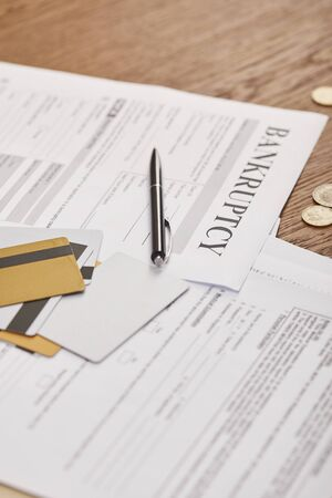 selective focus of bankruptcy form among documents, credit cards and coins on wooden table
