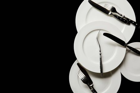 top view of white round plates with cutlery isolated on black with copy space 写真素材