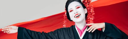 happy beautiful geisha in black kimono with red cloth on background isolated on white, panoramic shot 写真素材