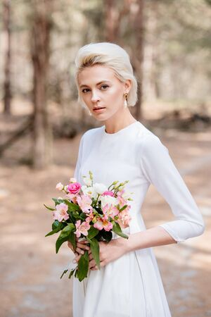 attractive blonde bride holding wedding bouquet in forest
