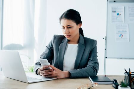 serious latin businesswoman using smartphone while sitting at workplace near laptop Foto de archivo