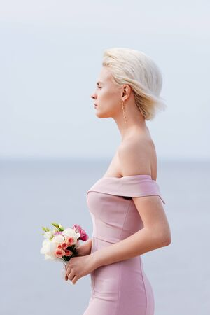 side view of pensive blonde girl in pink dress holding bouquet Stok Fotoğraf