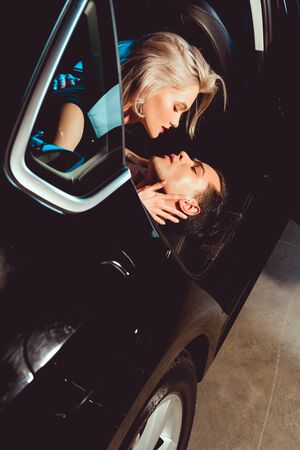 handsome man and attractive young woman embracing in car