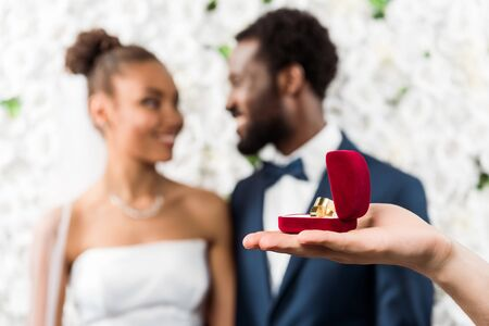 selective focus of man holding box with wedding ring near african american couple Stock Photo