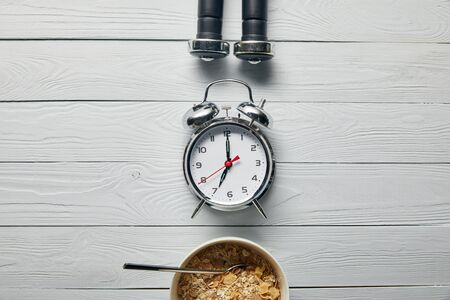 flat lay with silver alarm clock, breakfast cereal in bowl and black dumbbells on wooden white background