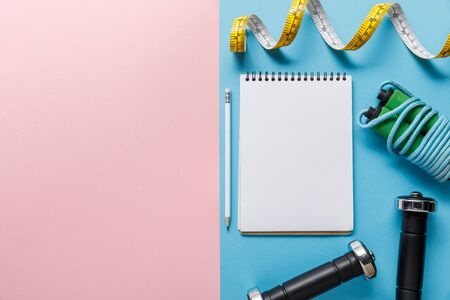 top view of blank notebook, dumbbells, skipping rope and measuring tape on blue and pink background