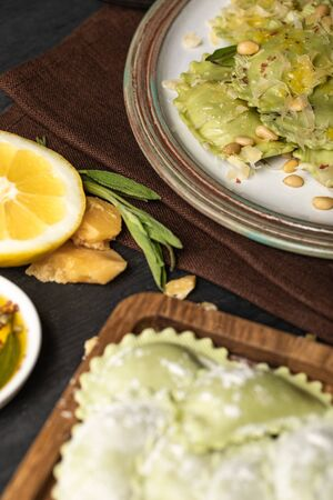 selective focus of green delicious ravioli with pine nuts on plate
