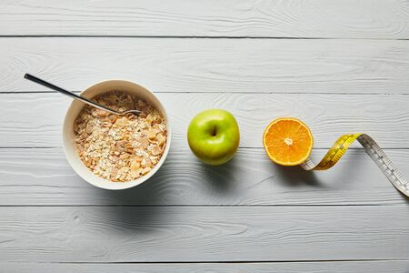 flat lay with breakfast cereal in bowl, apple, orange and measuring tape on wooden white background Stock Photo