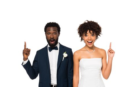 happy african american bridegroom and bride pointing with fingers isolated on white