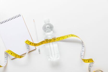 Draufsicht auf Wasser in Flasche, Maßband, leeres Notizbuch mit Bleistift auf weißem Hintergrund