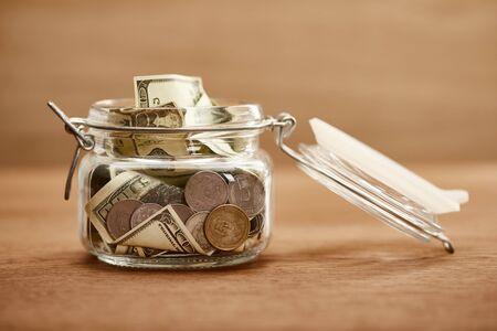 bocal en verre avec des pièces de monnaie et des billets en dollars sur une table en bois