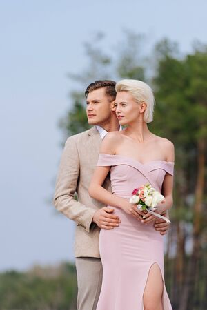 stylish couple with wedding bouquet embracing and looking away