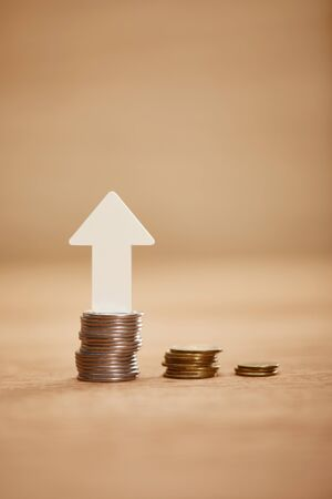 increasing chart made of coins with white arrow upwards, financial growth concept Stock Photo