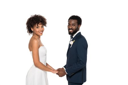 happy african american bride in wedding dress and bridegroom looking at camera while holding hands isolated on white 写真素材