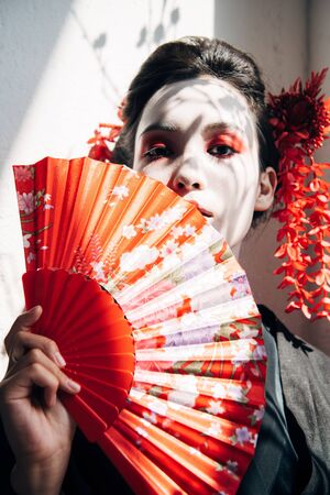 portrait of beautiful geisha with red and white makeup holding hand fan in sunlight